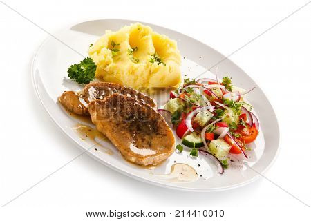 Fried pork chop, puree and vegetables on white background