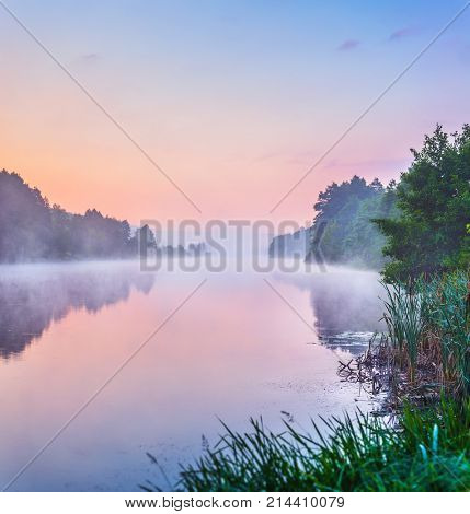 Landscape with sunrise and mist over river matutinal picturesque morning sky clouds in water sunbeam forest.