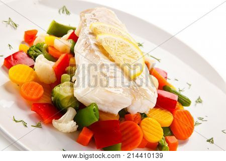 Fish dish - fried fish fillet and vegetables on white background