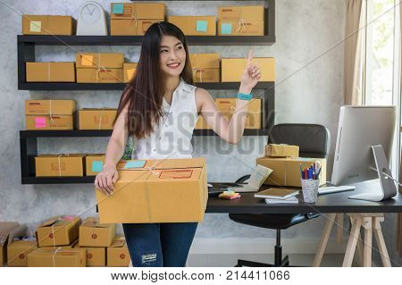 Young asian teenager owner business woman work at home for online shopping holding touching for present and the product with office equipment entrepreneur and alpha generation life style concept