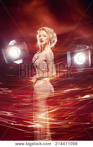 beautiful happy young woman with stunning figure and bright makeup wearing evening dress surrounded by light. studio lights. holiday mood. copy space.