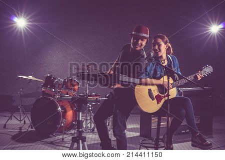 Musician duo band singing a song and playing music instrument with Fellow band musicians on black background with spot light and lens flare musical concept