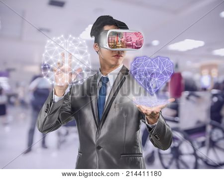 Asian Man wearing virtual reality in action hand holding the line of hearth shape and brain which can see Chemical Laboratory over photo blurred of hospital background VR technology concept
