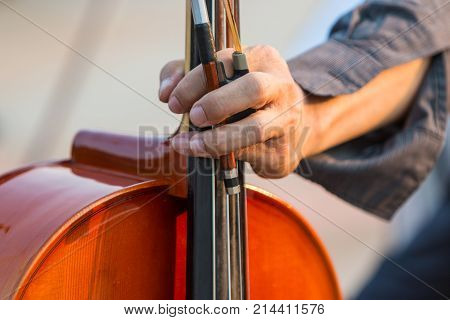 Close up of male cellist's hand holding cello and bow
