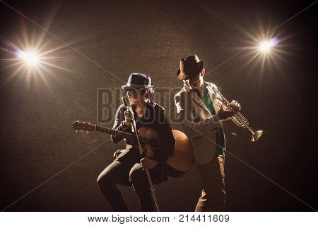 Musician Duo band playing a Trumpet and singing a song and playing the guitar on black background with spot light and lens flare musical concept