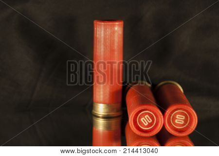 Three red shot-loaded cartridges from a hunting rifle on a dark background