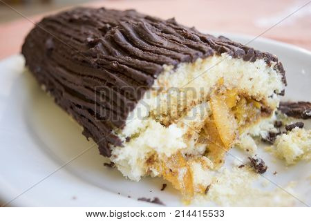 chocolate yule log cake with stuffing of cream and candied