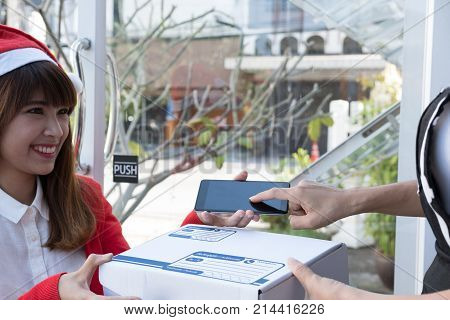 Courier Wearing Santa Claus Hat Delivering A Parcel Box To Customer During Christmas Holiday. Woman