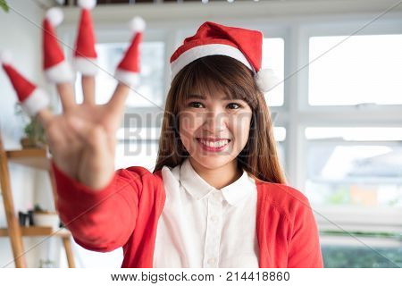 Woman Wear Santa Hat Shows Four Fingers. Asian Female Wear White Shirt And Red Knitting Cardigan Cou