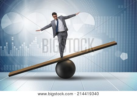 Businessman trying to balance on ball and seesaw
