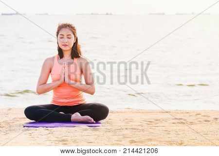 Asian woman close eyes and doing Hand namaste yoga pose and meditates on sand at coastline beach Calm and relax conceptwellness and healthy lifestyle