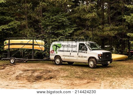 Canada Algonquin National Park 30.09.2017 Parked transporter of a canoe rental service at Lake two rivers Campground Beautiful natural forest landscape