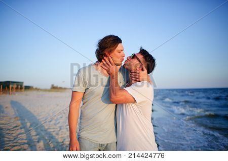 Two men embrace against the background of the sea. They represent a playful kiss.