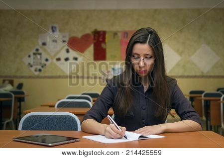 Pretty young female student in glasses sits at a desk in the classroom writes in a notebook and studies the teaching material. Education concept.