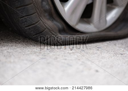 Car Tire Leak Because Of Nail Pounding. Flat Tyre On Road. Flatten Punctured Wheel