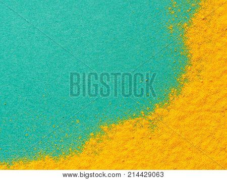 Turmeric Powder or Curcuma longa on green background. Top view. Copy space for text.