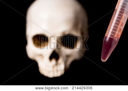 blood sample or other red liquid in testtube and blurry skull isolated on black background
