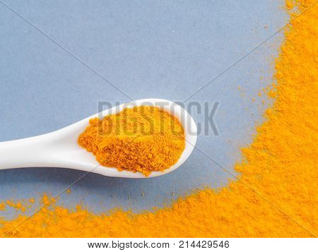 Turmeric Powder or Curcuma longa and white spoon with turmeric powder on gray background. Top view. Copy space for text.