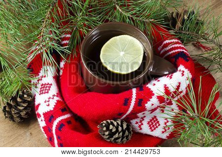 Hot winter tea in a brown cup with lemon. Christmas red scarf and xmas decorations - rural still life. Holidays at home.