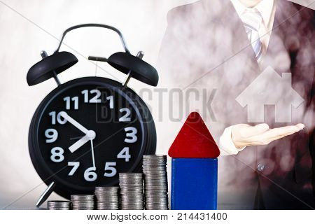Double Exposure House With Alarm Clock And Step Of Coins Stacks With House On Businessman Hand, Time