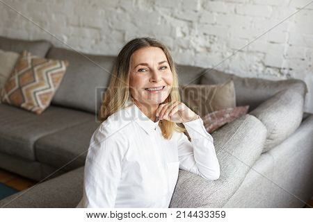 Charming elegant mature Caucasian female coach with loose hair smiling happily at camera rejoicing and success at work while consulting people on business. People age and occupation concept