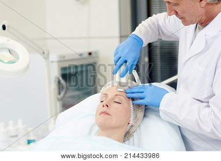 Modern cosmetician doing anti-wrinkle procedure on his client face