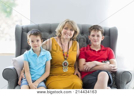 Mid-age woman with two young boys indoors. Family concept