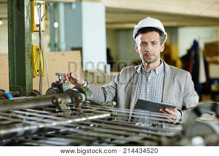 Foreman with touchpad working by industrial machine in modern factory