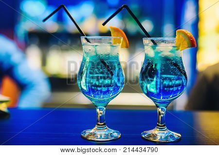 two glasses of blue cocktail Martini with orange and ice cubes and straws on the bar