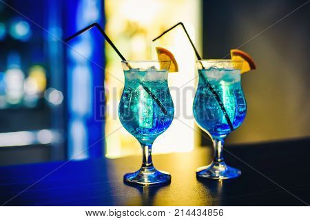 martinis in glasses with ice on the bar with orange and blurred background