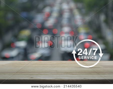 24 hours service icon on wooden table over blur of rush hour with cars and road Full time service concept