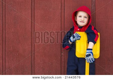 Young Boy Leans On His Toy Shovel