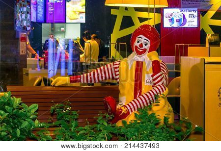 OM NOI THAILAND - OCTOBER 29: Statue of Ronald Mcdonald sits on a bench right outside of a local Mcdonald's store on October 29 2017 in Om Noi in Thailand.
