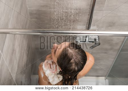 overhead view of girl washing shoulders in a shower with wisp of bast