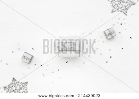 Three silver gift boxes snowflakes and confetti on white background. Winter Holiday card. Boxing Day concept. Diagonal decoration. Top view.
