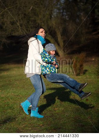 Young woman and boy 9-10 years have fun in the autumn park. Mom holds her son in her arms and turns around with him. A pleasant day a good mood.
