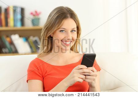 Girl Looking At Camera Holding A Smart Phone At Home