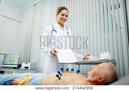 Young cardiologist looking at her patient before making ecg in clinics