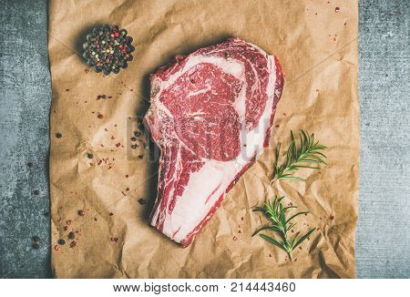 Flat-lay of raw uncooked prime beef meat dry-aged steak rib-eye on bone with seasoning on craft paper over grey concrete countertop background, top view. Meat high-protein dinner concept