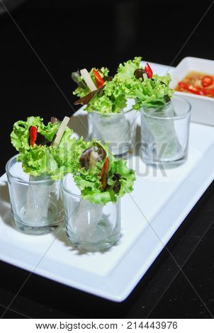 close up green salad row on white plate