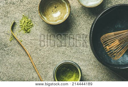 Flat-lay of Japanese tools for brewing matcha green tea. Matcha powder in tin can, Chashaku spoon, Chasen bamboo whisk, Chawan bowl and cups over grey concrete background, top view, copy space