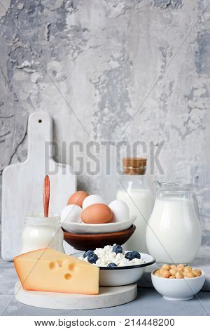 Dairy products on marble table over concrete background. Cheese, farmers cheese, milk, yogurt, sour cream, eggs and smoked cheese. Organic farmers dairy products