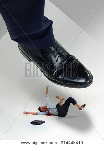 Aggressive boss pressing man by shoe. The suppression concept