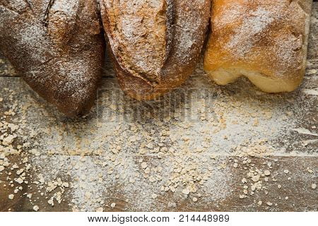 Variations of bread on the top of wooden table with flour, free space for text.  Flour as a main ingredient for cooking homemade bread.