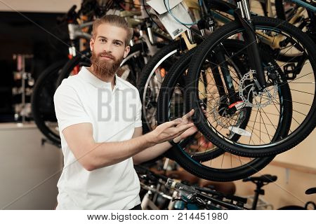 A salesman in a bicycle shop poses near a bicycle. There are parts, different types of bicycles. He smiles at the camera.