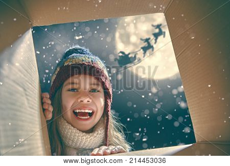 Merry Christmas and happy holidays! Cheerful cute child girl opening a present. Little kid having fun outdoors. View from inside of the box. Santa Claus flying in his sleigh against moon sky.
