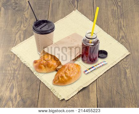 Two small pies with sweet toppings in fast food brown paper bag tea in the plastic container and disposable paper cup with plastic lid and drinking straws on a napkin on an old wooden surface