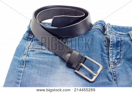 Casual black leather belt for men made of thick leather with classical buckle lies on a blue jeans on a white background