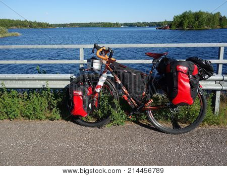 Lappeenranta Finland - June 29 2015: Adventure bike with mountain bike & touring bike capabilities and red panniers and other touring and camping gear attached to the bike by a lake Saimaa near Lappeenranta in Eastern Finland.