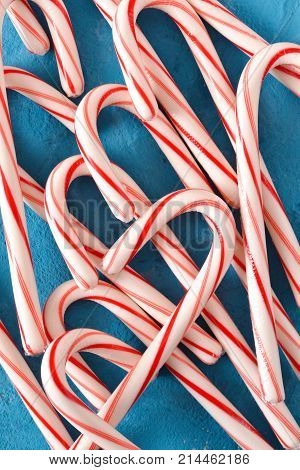 Candy cane on a blue background. Winter new year background.